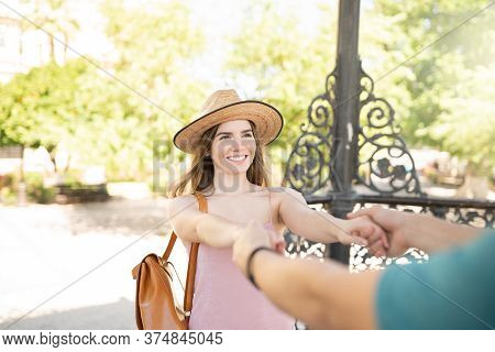 Happy Attractive Young Woman Holding Hands Of Boyfriend While Traveling Together