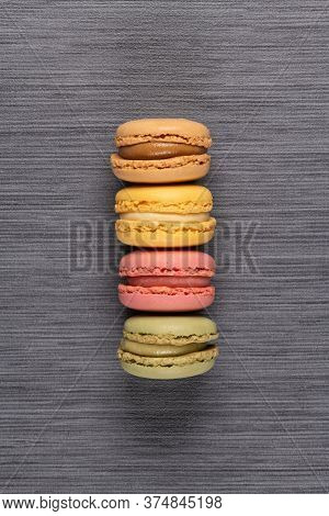 Four Delicious Macaroons On Grey Vinyl Background.