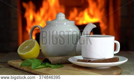 Cozy Fireplace,teapot And Cup Of Tea With Lemon And Mint On A Board Before Fireplace.