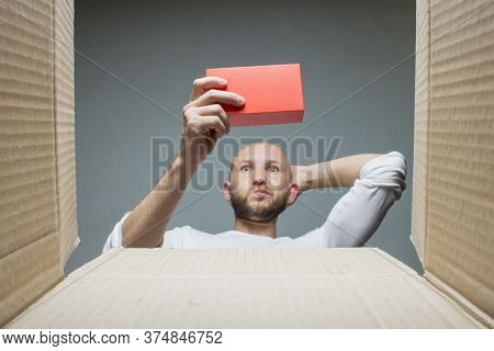 A Man With A Confused Face Holds The Goods Received. Inside View. Concept Received A Parcel, Order,