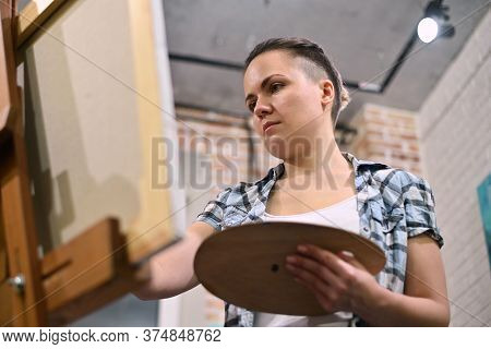 Bottom View Of A Woman Who Is Painting In A Studio. Enthusiastic Artist At Work