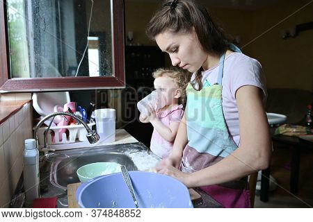 A Young Woman Is Busy Cooking, While Her Little Daughter Is Playing Nearby. Mom And Baby Doing House