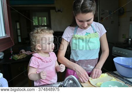 A Little Girl Plays With Flour In The Kitchen Sink Next To Her Mother, Who Is Preparing Dinner. Merr