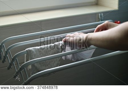 A Woman Hangs Washed Baby Clothes On The Dryer. Moms Daily Routine. Close Up