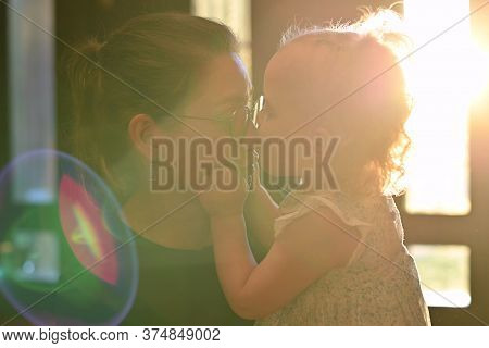 Little Girl Kisses Her Mother In The Bright Ray Of Sunshine, Which Breaks Through The Window On A Su