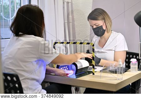 The Master In A Protective Mask And Gloves Serves The Girl In A Beauty Salon. Work With Clients In C