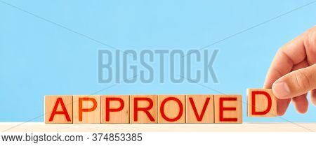 Approved Concept. Man Stacks Wooden Blocks In The Inscription Approved