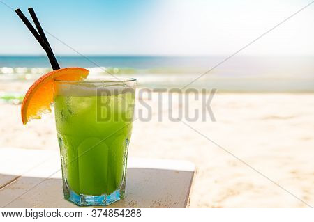 Bocal Of Fruity Cocktail On A Beach Table. Exotic Summer Drinks
