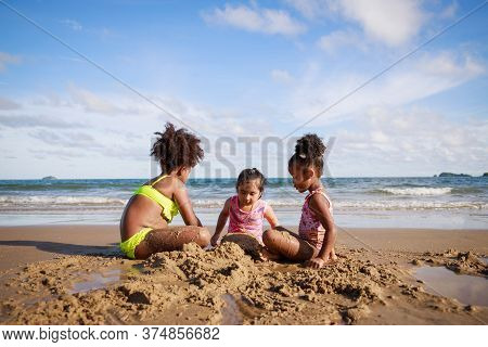 Happy Friendship. Happy Vacation Holiday. Happy Three African American Kids Are Building A Sandcastl