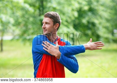 Front View Of A Sportsman Stretching Hands While Standing Outdoor In A Park And Looking By Side. The