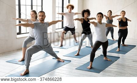 Young Male Trainer Leading Yoga Class For Concentrated Multiracial Students.