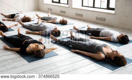 Diverse Fit People Relaxing In Renovative Savasana Pose.
