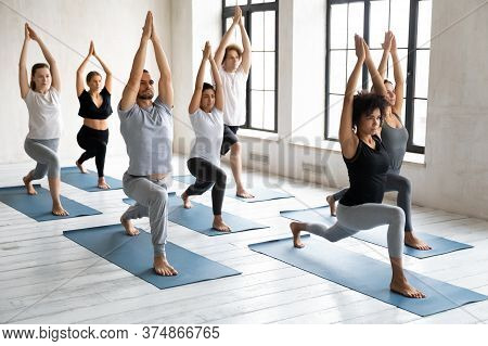 Motivated Focused Young Multiracial Diverse People Standing In Virabhadrasana 1 Pose.