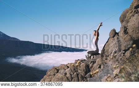 Woman Doing Yoga And Meditating On Background Of Natural Landscape