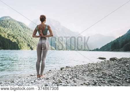 Young Woman Is Practicing Yoga At Mountain Lake. Girl Doing Yoga On Nature. Healthy Lifestyles. Conc