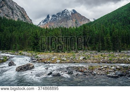Atmospheric Beautiful View To Mountain River, Snowy Mountain And Conifer Forest In Overcast Day. Glo