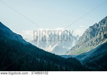 Tranquil Landscape With Great Snowy Mountains And Coniferous Forest On Mountainside. Beautiful Atmos