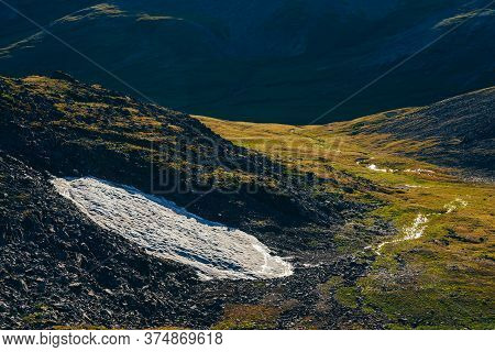 Vivid Scenery With Small Glacier On Hillside In Green Mountain Valley In Sunlight. Snow On Rocky Slo