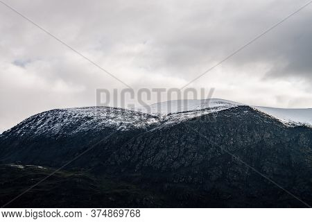 Great Black Mountain With White Snow On Top. Black And White Dramatic Landscape With Snowy Mountain