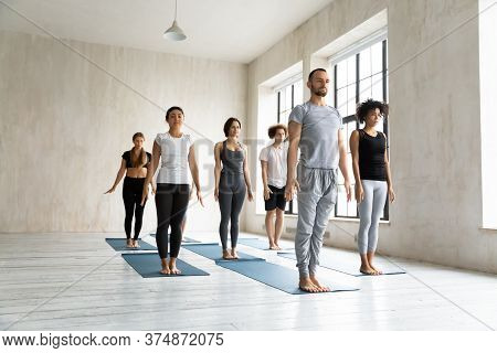 Young Male Instructor Leading Yoga Class, Standing In Mountain Pose.