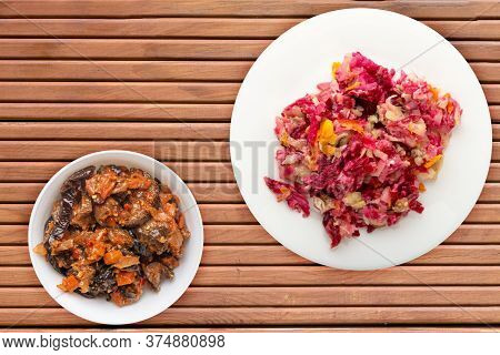 Herring Under A Fur Coat On A White Plate. Herring Under A Fur Coat On A Orange Wooden Background. H