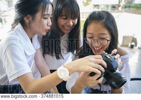 Three Asian Teenager Looking Photo On Dslr Camera Screen  With Happiness