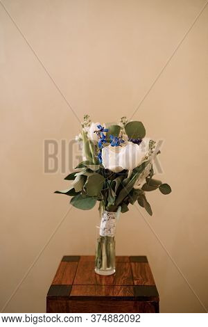 Bridal Bouquet Of White Tulips, Delphinium, Salal, Limonium And Lace Ribbons In Glass Vase On The Wo