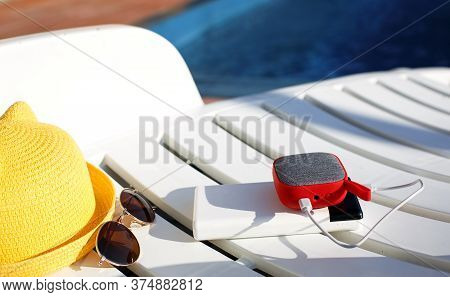 Music Portable Speaker Is Charged From The Power Bank Via Usb On A Deck Chair Near The Pool With Bea