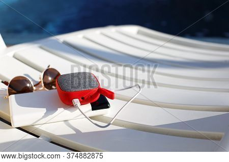 Red Music Portable Speaker Is Charged From The Power Bank Via Usb On A Deck Chair Near The Pool. Con