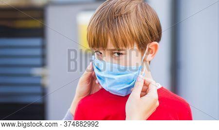 Coronavirus Quarantine. Coronavirus Outbreak. Mother Puts Her Son A Face Protective Mask Outdoors. S
