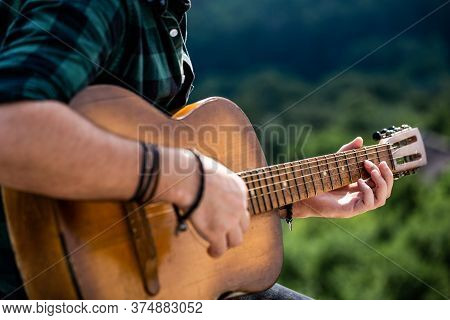 Male Musician Playing Guitar, Music Instrument. Mans Hands Playing Acoustic Guitar, Close Up. Acoust