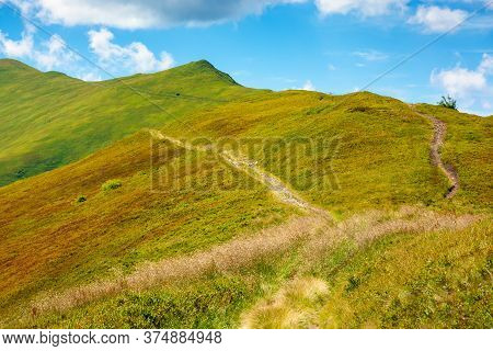 Trail Uphill Through Mountain Range. Grass On The Hills And Slopes. Summer Landscape On A Sunny Day.