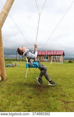 Child Swinging On Swing At Outdoor Playground