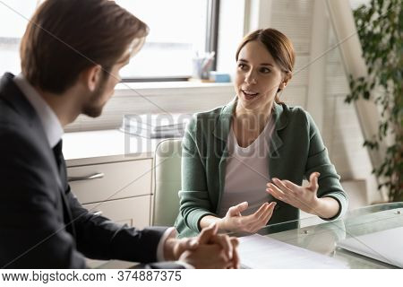 Motivated Female Employee Talk Discuss Ideas With Colleague