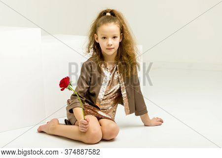 Beautiful Girl Sits With Her Head Bowed To The Side, Studio Portrait Of A Cute Baby Kneeling In A Sh