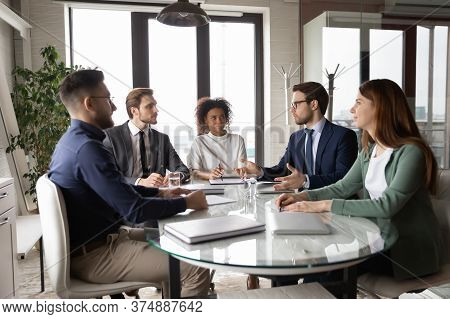 Multiracial Employees Gather In Boardroom Engaged In Team Discussion