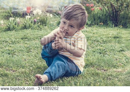 A Pretty Child Bites His Toenails. A Two Year Old Kid Will Put His Dirty Foot In His Mouth. A Boy Si
