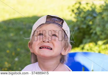 Portrait Of A Beautiful Two Year Old Baby In A Baseball Cap. A Boy With Blond Hair Is Carefully Look