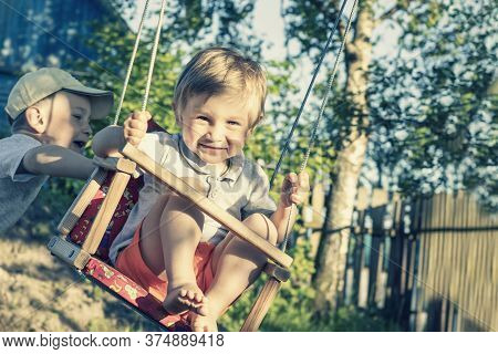 A Handsome Joyful Boy Of 2 Years Old Is Swinging On A Swing And Smiling. The Older Brother Pushes Th