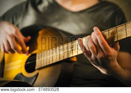 A Man In A Gray T-shirt Plays A Tune On A Decrepit Old Acoustic Guitar, Illuminated By The Light.
