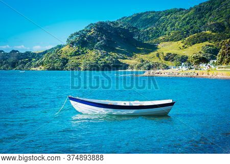 A Wooden Row Boat Moored In Calm Waters Of The Bay On A Glorious Summer Day.