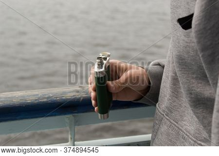Handsome Young Man Holding The Freen Flask Near The River Water. Selective Focus On Flask