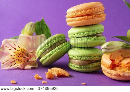 Few Green And Yellow French Macaroons And An Alstroemeria Flower On A Purple Background, French Cook