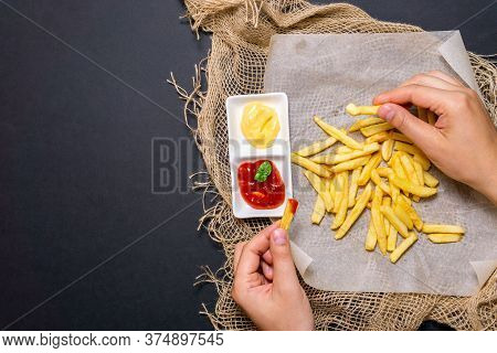 Fries-fried Potatoes On A Black Background With Cheese Sauce. Eating A Mans Hands.