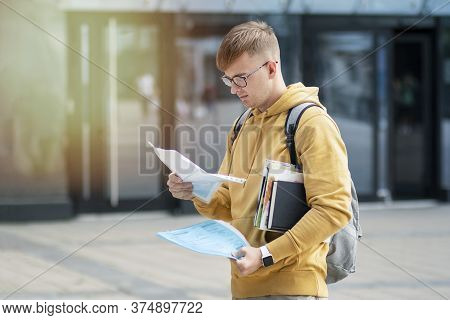 Young Handsome Guy, Serious Focused Student With Backpack In Glasses Standing Outdoors With Books An