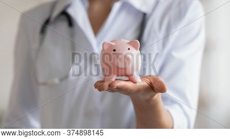 Close Up Of Female Doctor Hold Piggybank Collect Donation