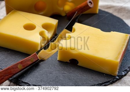 Block Of Swiss Medium-hard Yellow Cheese Emmental Or Emmentaler With Round Holes And Cheese Knife