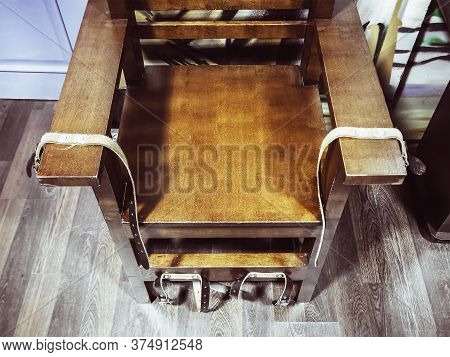 Old Wooden Chair With Shabby Leather Straps Attached To The Armrests And Legs. Chair For Torture. An