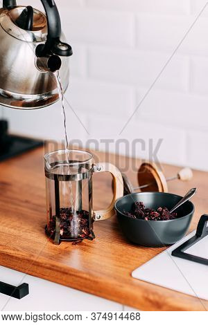 Loose Hibiscus Tea Brewing In French Press With Hot Water. Pouring Water From Metallic Teapot. Brigh