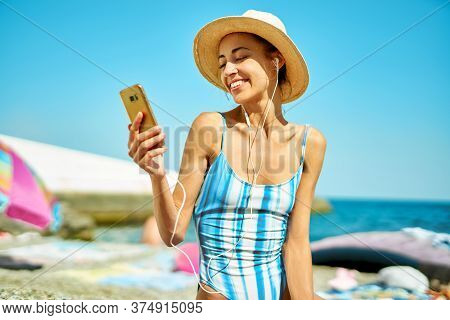 Happy Woman In Straw Hat And Swimsuit At Beach Communicating On Smartphone, Online Video Cell Phone